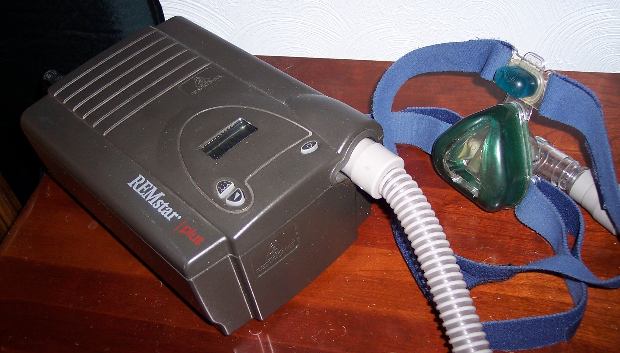 A typical CPAP machine houses the air pump in a case lined with sound-absorbing material for quieter operation. A hose carries the pressurized air to a face mask or nasal pillow.