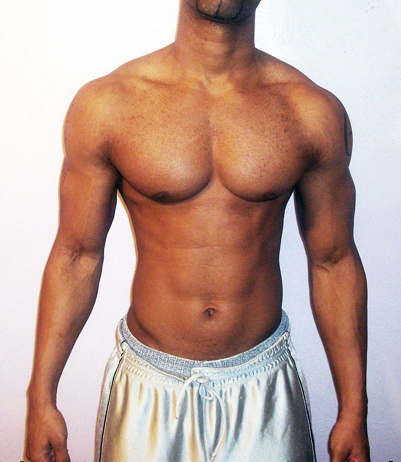 An adult man with pronounced shoulder width and expanded chest, both traits typically associated with male physique.
